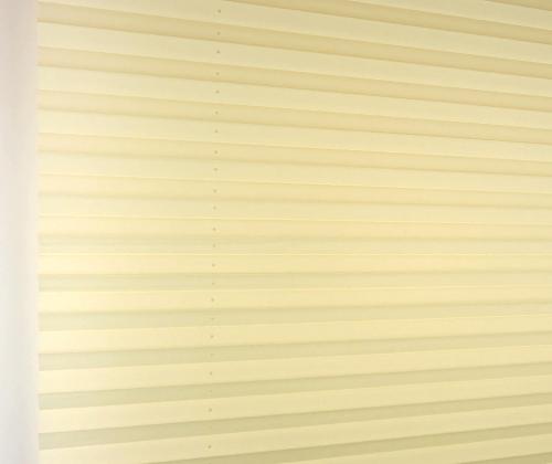 Het plissè gordijn crème wanneer deze uitgevouwen is